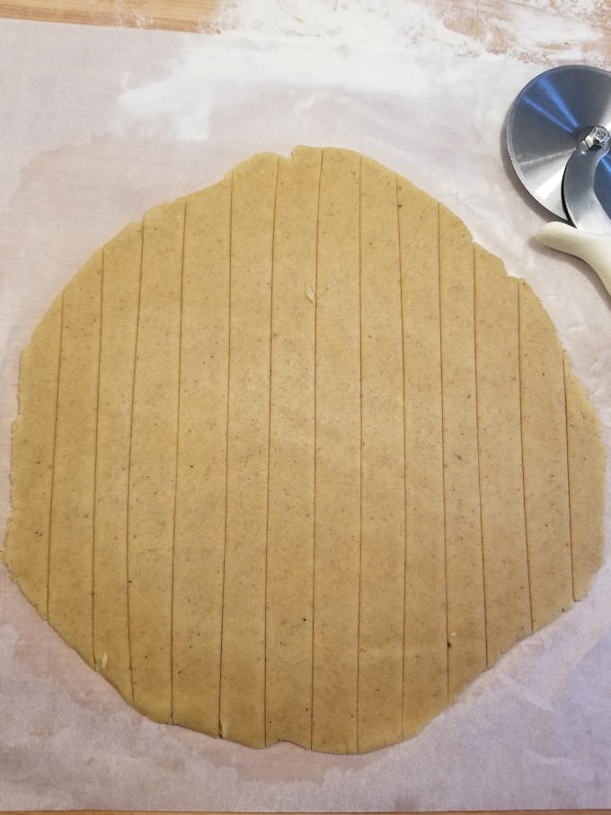 cut strips of dough to make a lattice top on apple walnut linzer tart