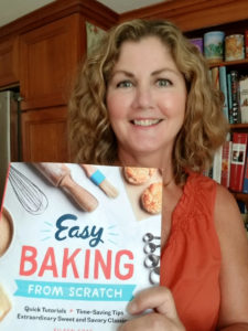 Author holding copy of cookbook