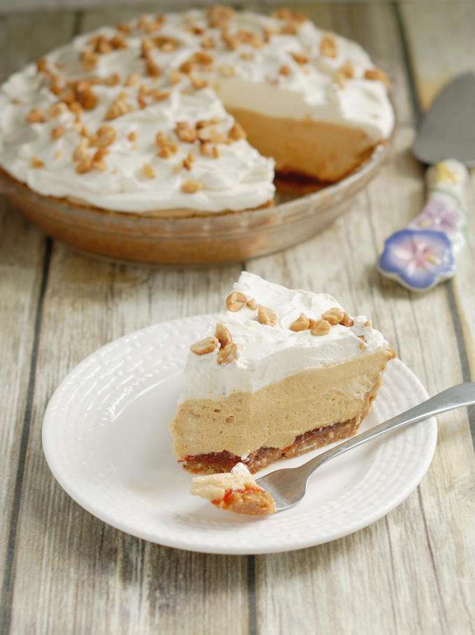 A slice of peanut butter mousse pie with cream and honey roasted peanuts on top