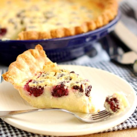 a slice of blackberry buttermilk pie on a white plate with a fork
