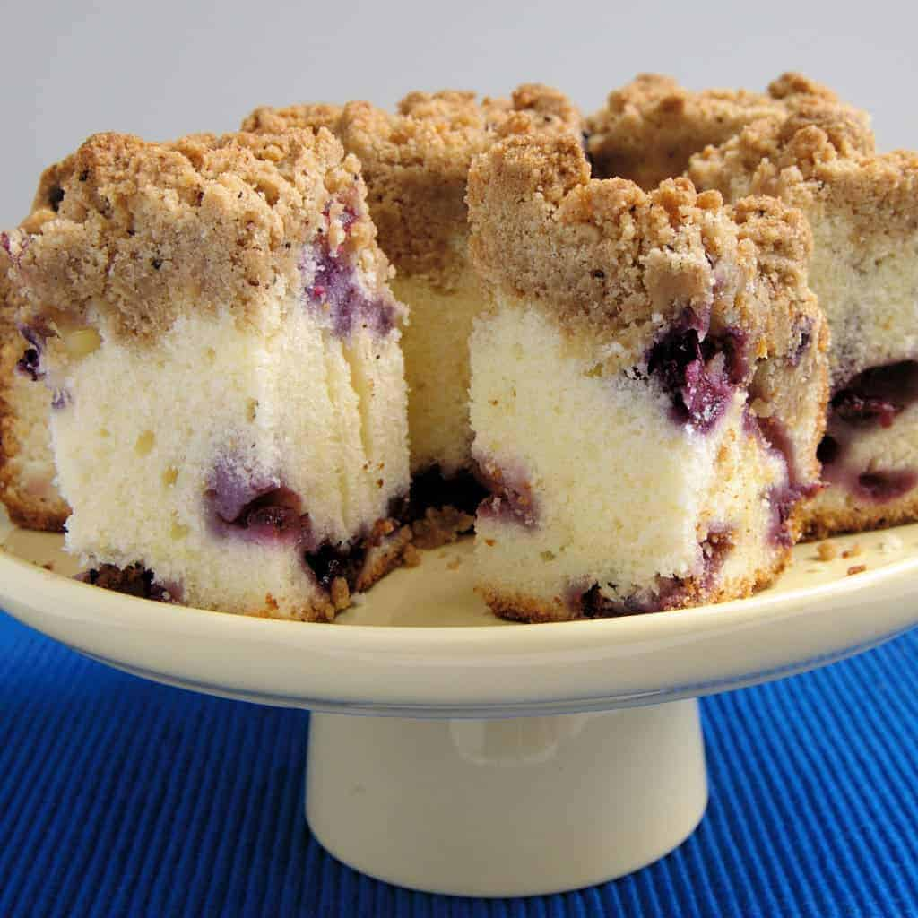 a Blueberry Crumb Cake on a cake stand