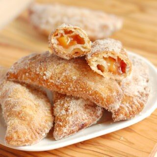 A plate of fried peach hand pies with one open at the top