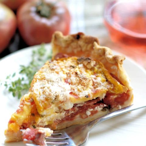 A slice of tomato pie on a white plate with a fork and a sprig of herbs