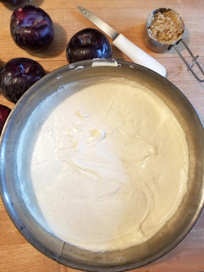 cake batter in a pan with plums on the side