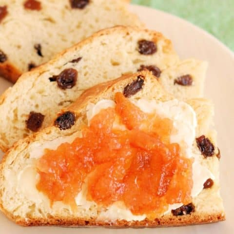 A closeup shot of three slices of Irish soda bread with raisins. One slice has butter and orange marmalade on top.
