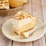 a slice of pumpkin mousse pie with toasted meringue. A fork with a bite on pie is on the plate.