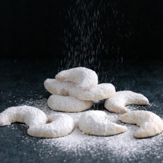 a pile of vanilla kipferl cookies on a black background with sugar pouring down