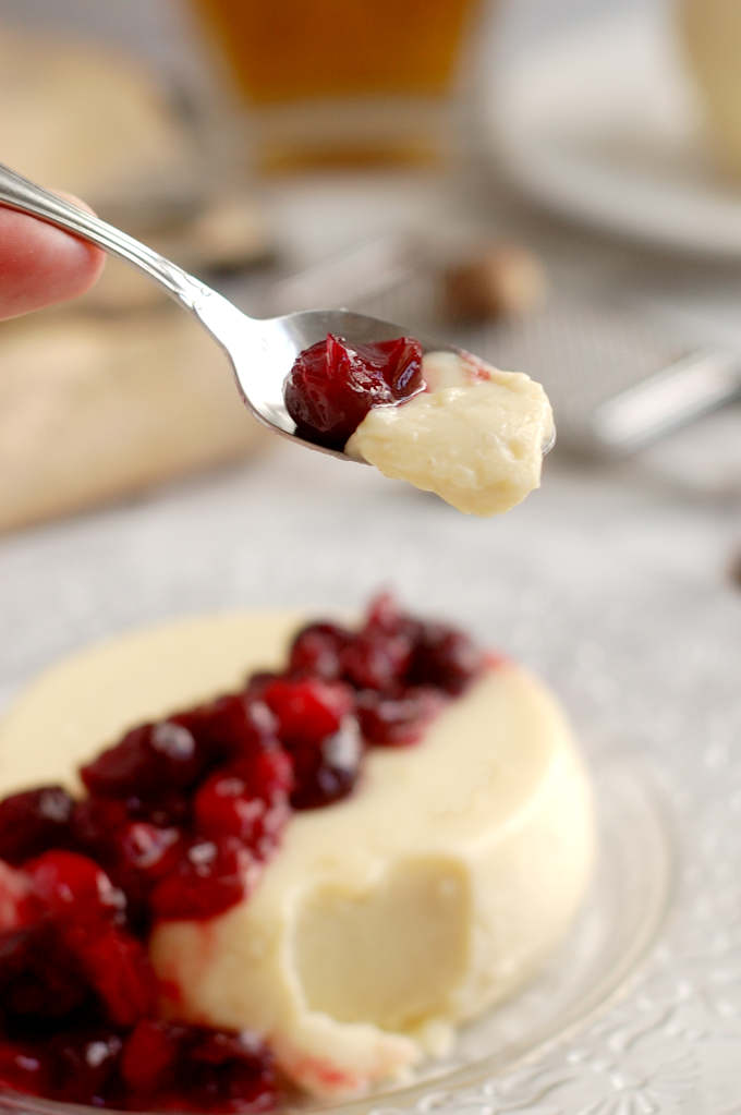 a spoonful of eggnog panna cotta with cranberries