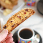 a hand holding a triple ginger cranberry biscotti