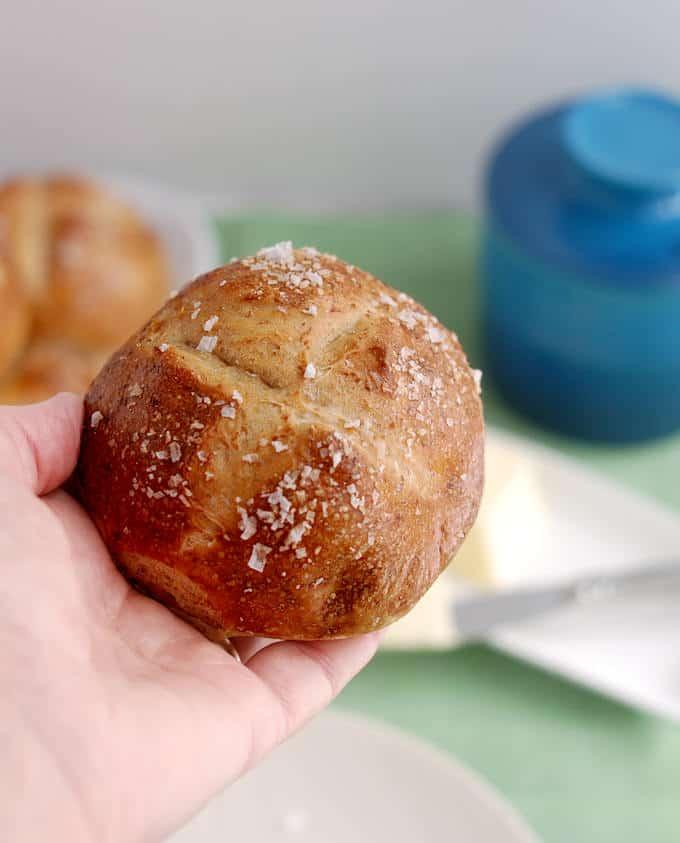 a hand holding a malt and rye pretzel roll