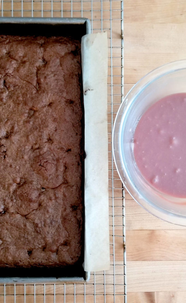 a pan of chocolate cherry brownies and a bowl of cherry ganache