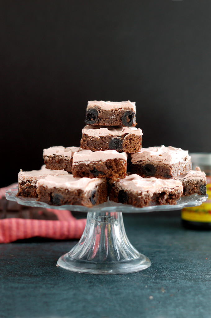 a cake stand with chocolate cherry brownies stacked on top