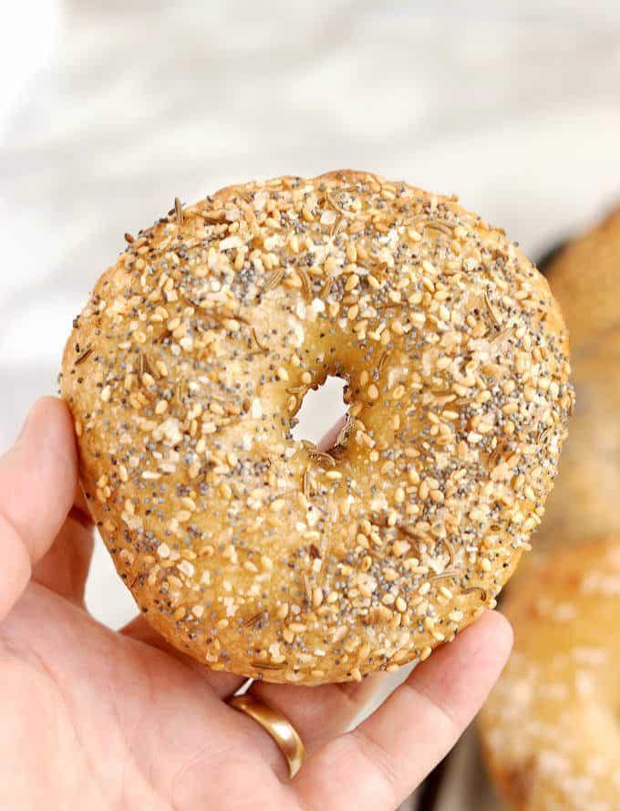 a hand holding a sourdough bagel