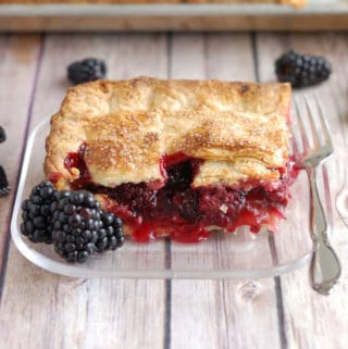 a slice of berry pie on a glass plate