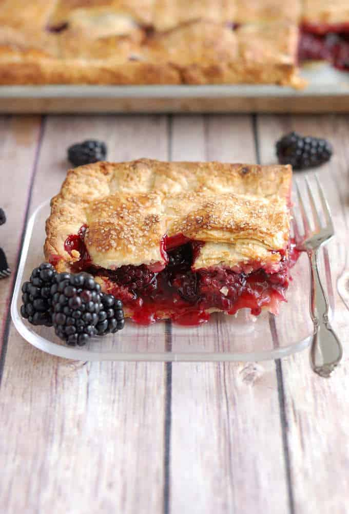 A closeup shot of a piece of blackberry pie with a fork on a glass plate.