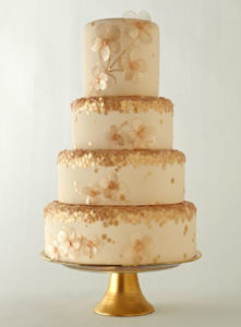 A four tier ivory and gold wedding cake with glitter and flowers