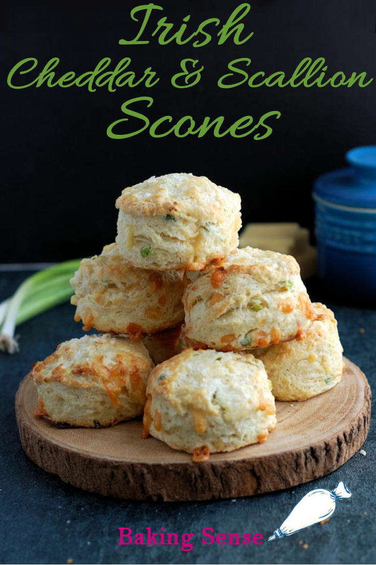 A plate of stacked with scones against a dark background. Green text overlay says Irish Cheddar & Scallion Scones