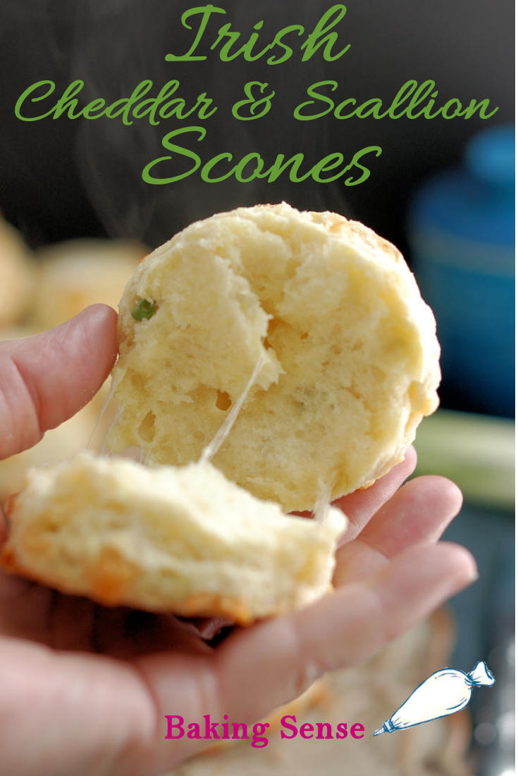 A closeup shot of a warm scone opened up with melting cheese and steam against a dark background. Green text overlay says Irish Cheddar & Scallion Scones