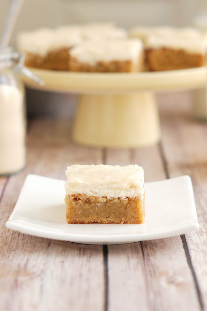 a malted milk blondie with malted milk frosting on a white plate