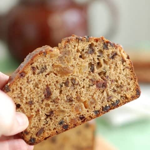 a hand holding a slice of Irish Tea Brack