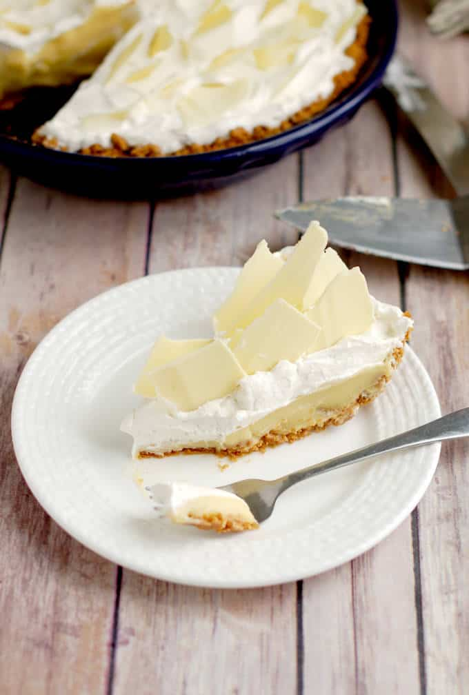 a slice of malted milk cream pie on a white plate with a fork