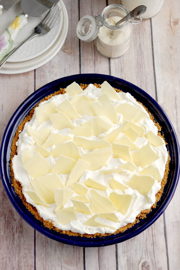 a malted milk cream pie in a blue pie plate set on a wood table.