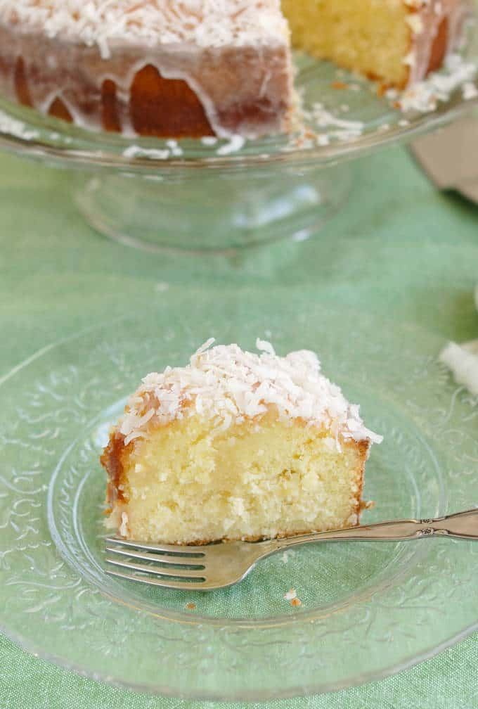 a slice of coconut pound cake on a plate with a fork.
