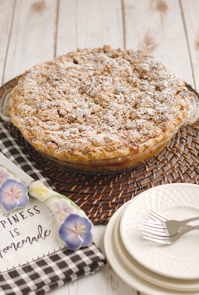 a freshly baked rhubarb crumb pie on a table with serving dishes.
