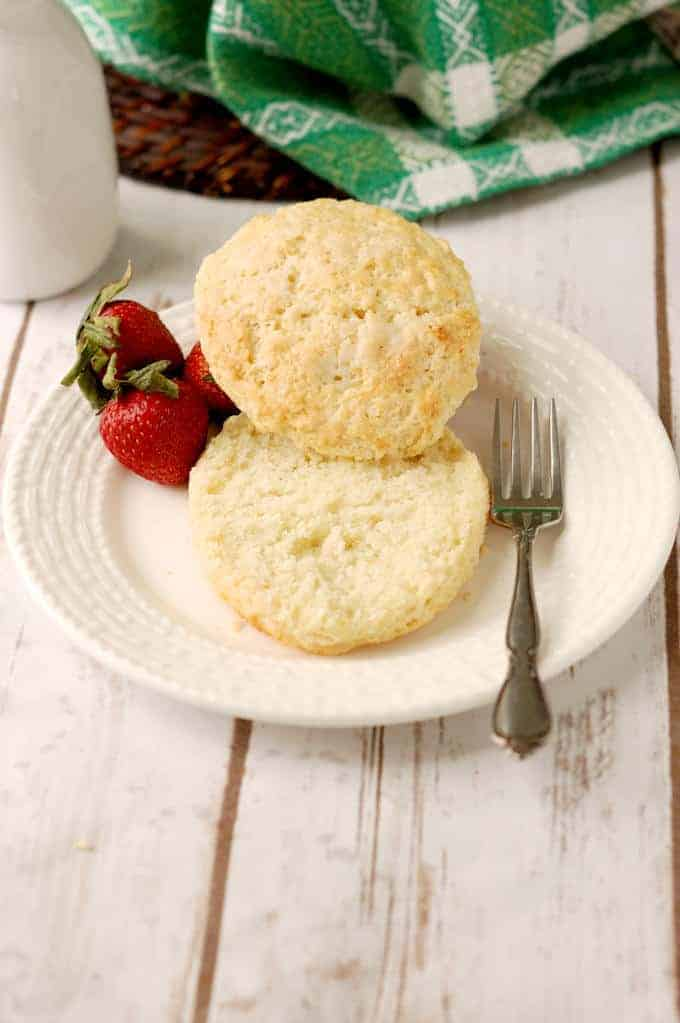 a split shortcake biscuit on a plate with strawberries