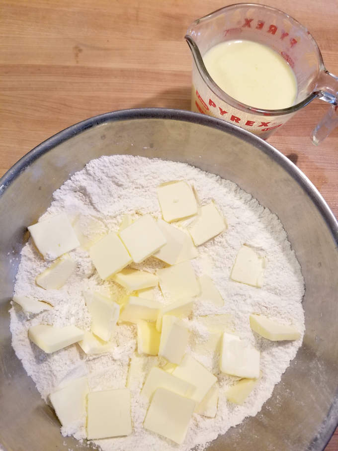 a bowl of flour with chunks of butter on top with a cup of buttermilk on the side.