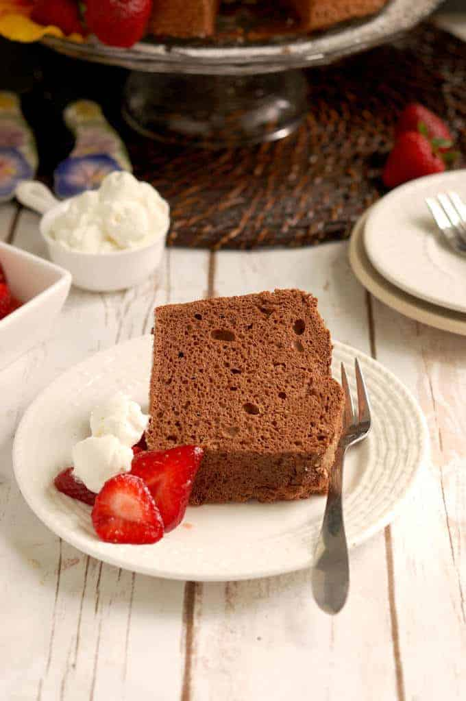 a slice of chocolate angel food cake on a plate with cream and strawberries