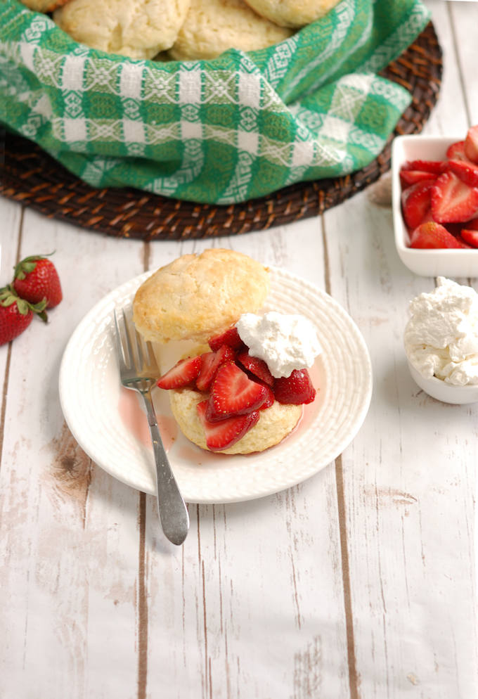 a table with the makings of strawberry shortcake and a plate with a strawberry shortcake