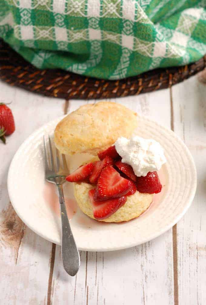 a plate with a strawberry shortcake with cream