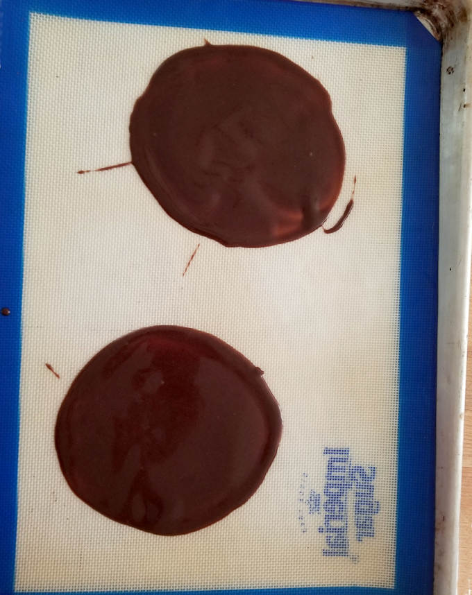 a baking tray with two chocolate cookies spread very thin