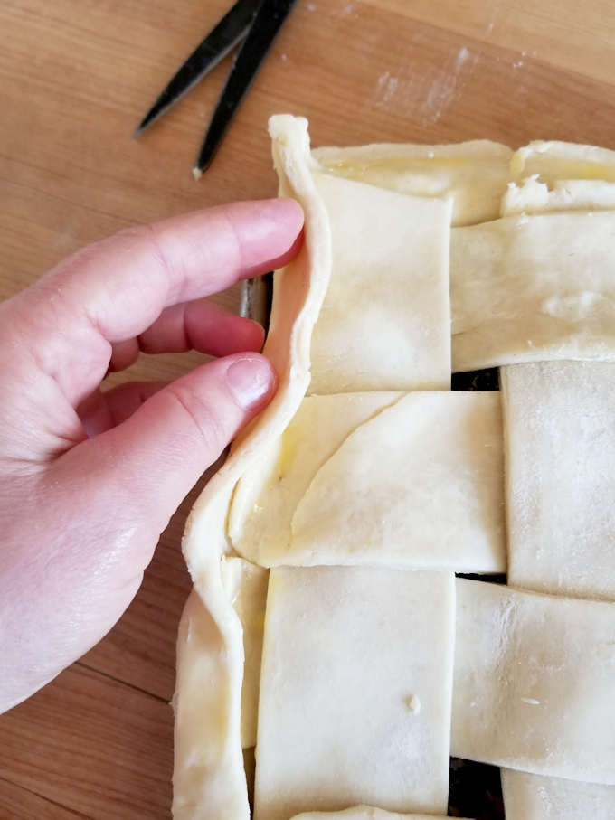a hand folding the edge of a pie crust