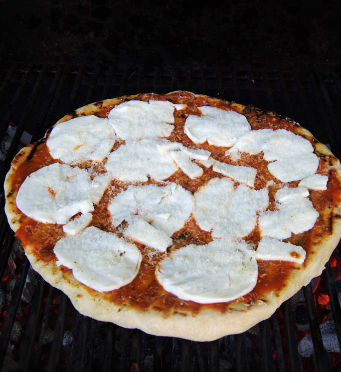 a pizza with tomato sauce and mozzarella on a grill