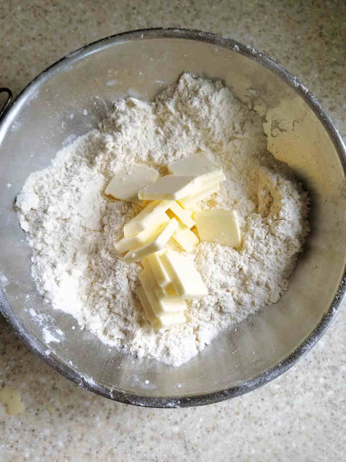 a bowl of flour with slices of butter on top