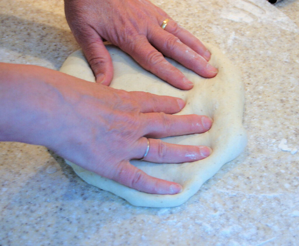 Forming pizza dough by hand
