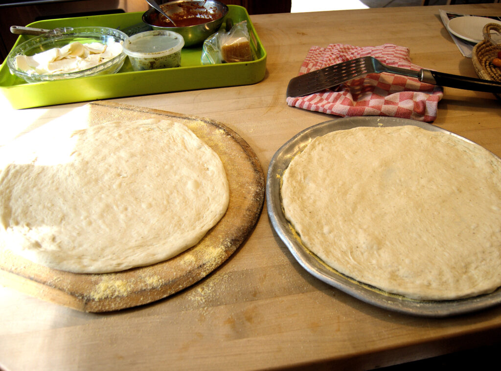 two pizzas ready for topping