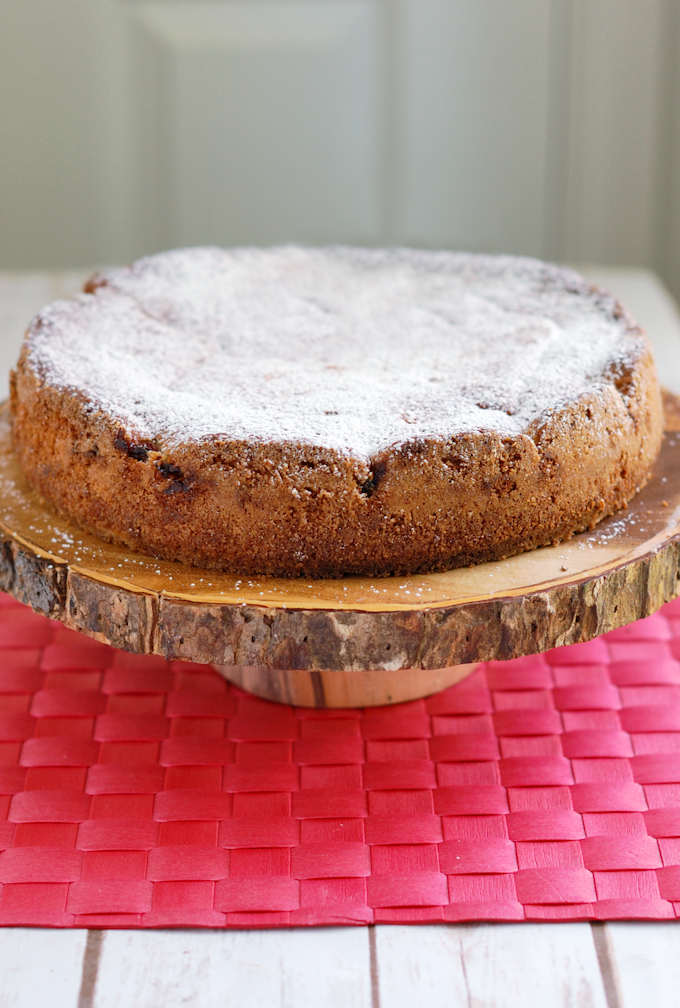 a sour cherry cake on a wooden cake stand