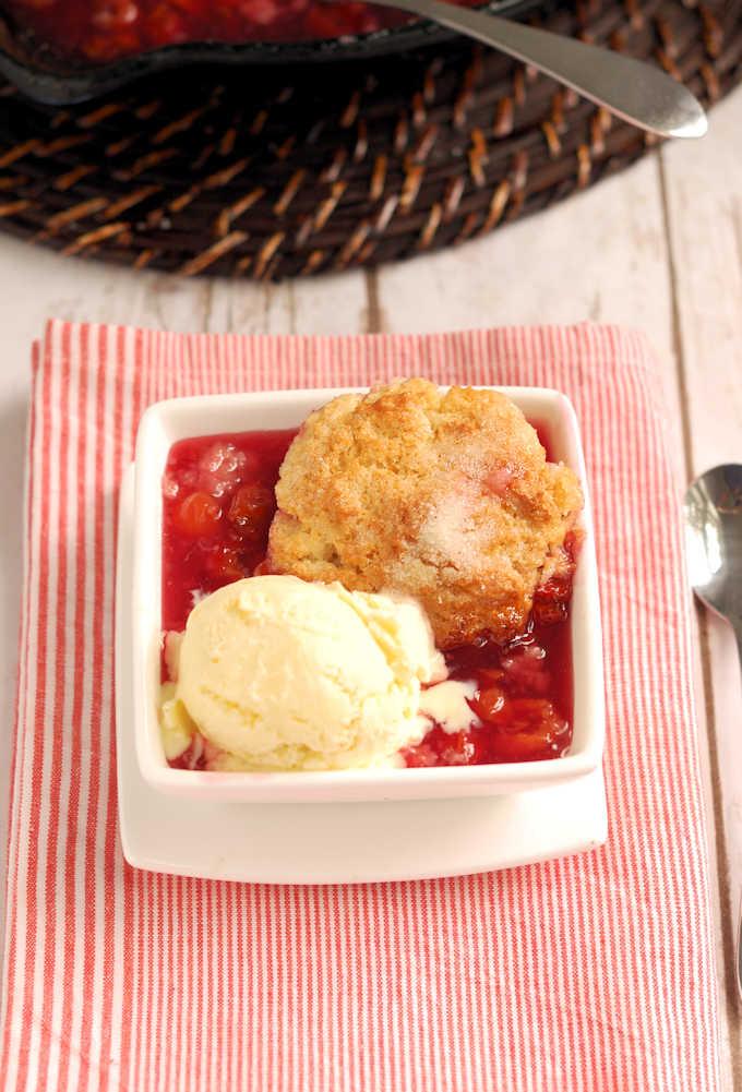 a bowl of cherry cobbler and vanilla ice cream