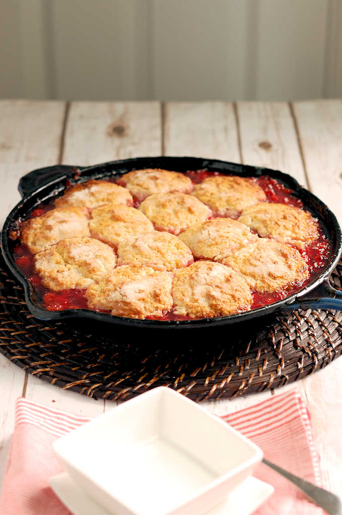 a cast iron skillet with sour cherry cobbler
