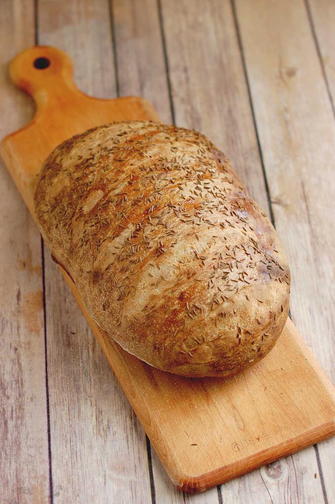 a loaf of sourdough rye bread on a cutting board