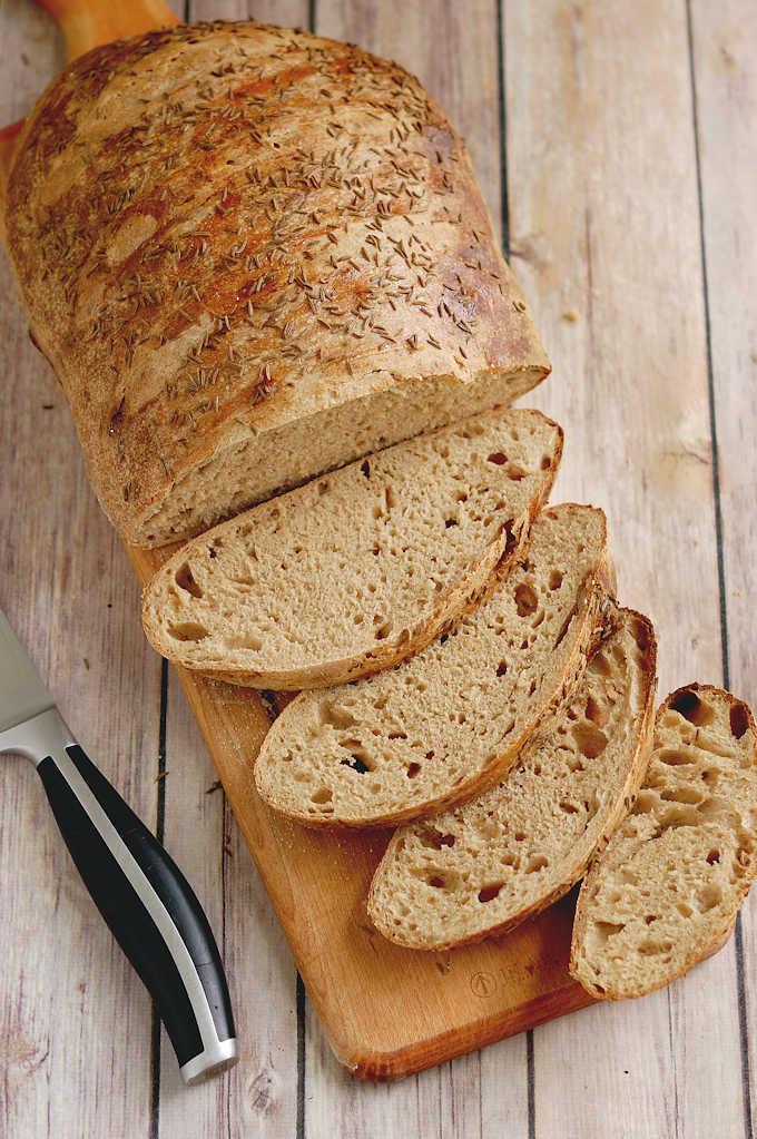 a loaf of sliced sourdough rye bread on a cutting board.