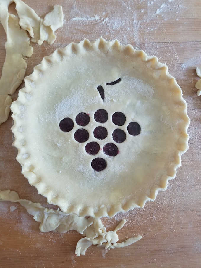 an unbaked concord grape pie on a wooden table