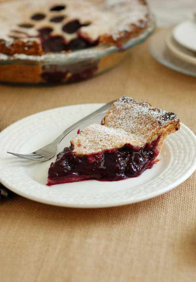 a slice of concord grape pie on a white plate with a fork