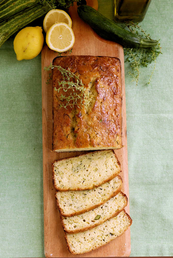 a cutting board with a sliced loaf of lemon zucchini bread with olive oil and thyme