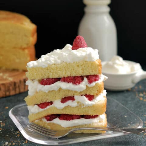 a slice of vanilla cake with raspberries and cream on a plate