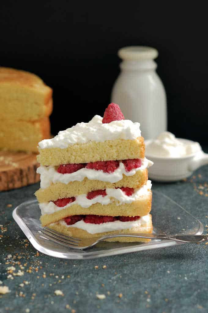 a slice of vanilla cake with raspberries and cream on a plate.
