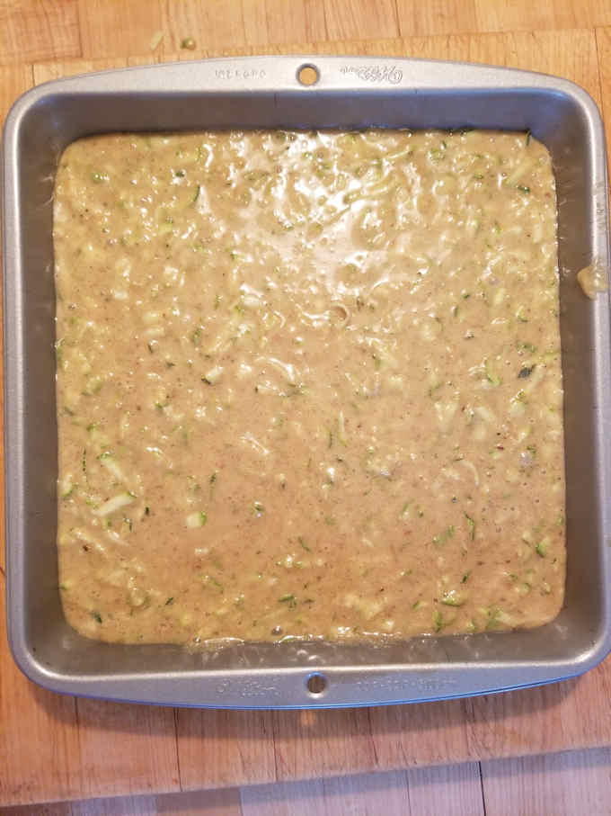 zucchini cake batter in a square cake pan